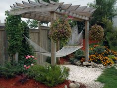Look close at the detail in the different lenghths and arched header.Want to make this pergola but to hang our 2 hammock chairs.  Love the hooks for hanging plants.  Would be great with trellis panels on the back for privacy against the neighbors' yard
