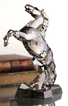 "Swarovski Stallion, Satin   $1,020.00 	8 7/16"" 		  Item# 1074793  Dynamic and expressive, this stunning Soulmate sculpture captures the power and beauty of the stallion in motion. Shining in Crystal Satin on a Caffee Brown granite base, the stallion makes a strong statement in any surroundings. It comes with a cleaning cloth, gloves and card describing the animal's character."