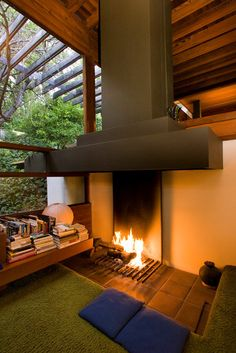 The living room fireplace, like the rest of the house, is open. The ratio of glass to floor area is about 50-50, predating later California residential code that limited glass to 20% and furthering the feeling of the house adrift in nature.