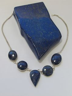 Handmade artisan necklace with 5 natural polished Lapis Lazuli cabachon stones including pear-shaped center stone, bezel-set in 925-hallmarked sterling silver with lobster claw clasp. Matching bracele