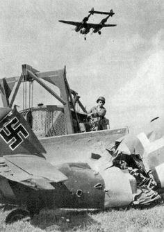 An allied P-38 Lightning flys over the wreckage of a German plane.