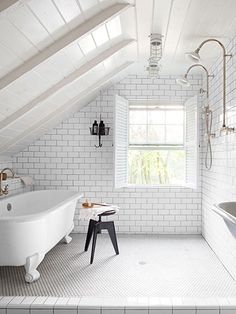 A Victoria + Albert tub sits opposite the showers, all finished with fittings from Habitat, a local Pennsylvania hardware store.