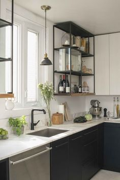 overhauled Ikea Akurum cabinets, electro-painting them with a resistant black matte coating. To create a streamlined effect, he capped the cabinet doors with the same finish as the metal appliances and added handles.