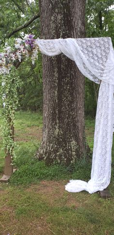 Light brown arbor with lace draped over one side and flower arrangement and greenery over the other side
