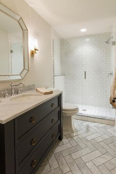Gray marble herringbone tiles cover floors framing a gorgeous washstand painted in Benjamin Moore Hale Navy donning brass ring pulls and Carrera marble countertops holding an oval sink and polished nickel vintage cross handle faucet sat below a beaded beveled vanity mirror lit by a brass sconce.