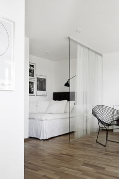 50m² apartment: Living/Bed room - The solid wall that closed the alcove to hide the bed was removed, in favor of a glass wall lined with a sheer fabric lightly hiding the sleeping area and allowing it to receive the light of day.