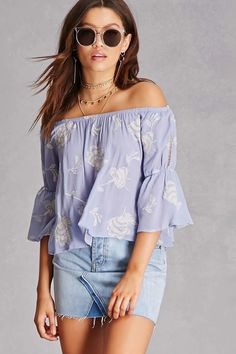 A woven top by Lust™ featuring an elasticized off-the-shoulder neckline, allover floral embroidery, 3/4 sleeves with elasticized arm bands and crochet ladder inserts, and a flowy silhouette.