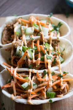 Bbq pulled pork with an asian flair! These taco boats start with pork that is slow cooked in an Asian inspired sauce then topped with cucumbers, carrots and Sriracha mayo! lemonsforlulu.com ad