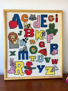 Vintage Nursery Art Needlework Alphabet Wall Hanging - Adorable brightly colored alphabet with animals and objects - Hand stitched in a wooden frame - Red, yellow, blue, pink, green, orange, grey - most of the colors - Animals include frog, mouse, rabbit, snake, zebra - Objects include: umbrella, kite, top hat, apple  Measures: 16.8 x 19.75 x 1.25  CONDITION REFERENCE CHART RATING: Very Good Frame could use TLC or replacement. It has some damage bottom right corner, and a couple tiny spots…