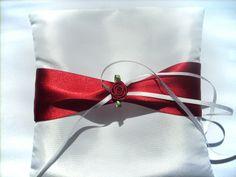 Polštářek pod prstýnky Smetanový polštářek sčervenou stuhou a květinou.