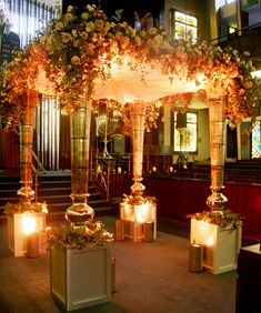 Chuppah with brushed metal vases on plinths, with Memory Lane, Quicksand, Majolica, Bombastic and Amnesia roses with trailing Eucalyptus and...