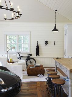 Garage with plank walls, wide plank hardwood flooring (yes, really!), chandelier and man's cave.