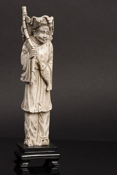 FIGURE OF A FISHERMAN Oriental sculpture in ivory. Base in wood. 20th Century.Dim: 23 cm. (total)