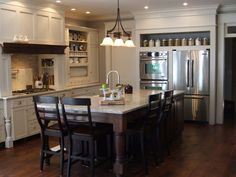 Love the furniture style look created here.  The table legs added to existing cabinets and the shelf above the fridge