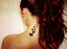 Pequeño tatuaje en la nuca de varias mariposas volando.