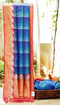 THE CHECKERED SHADES OF BLUE BENARES KORA WITH CONTRASTING RED BORDER AND PALLU THAT HAS INTRICATELY WOVEN GOLD AND SILVER ZARI FLORAL BORDER THAT MAKES THE SARI SUBLIME.