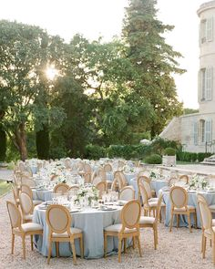 A Chic, Family-Oriented Destination Wedding in France | Martha Stewart Weddings - The couple's elegant wedding reception was held outside between rose gardens and the château's façade. Guests sat at round tables set with custom blue cotton tablecloths and upholstered chairs. #destinationwedding #wedding #weddingcolors