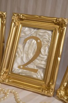 Table number idea: The style of frames you like, framed textured fabric, gold number.