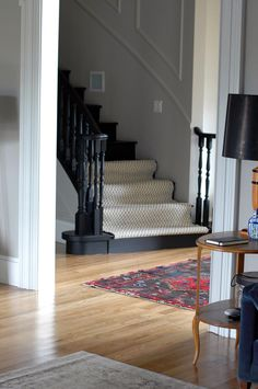 My style the gray walls, black stairs, white trim, black and white modern runner, and pop of red with the rug