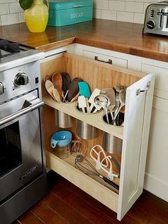 pullout shelf in kitchen cabinets with storage room for cooking utensils like spatulas #cookingutensils