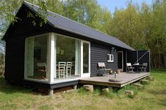 Modular prefabricated cottages with tar-treated larch wood exteriors and Scandinavian designed interiors by the Danish architectural firm Lykke + Nielsen.