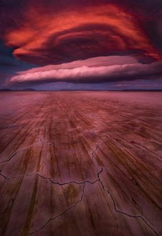 Fireball - sunset on a barren desert playa on the Oregon/Nevada border.  The foreground is drying cracks and streaks left behind by muddy water blowing across the plain. Photography by Marc Adamus