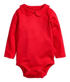 Red. CONSCIOUS. Long-sleeved bodysuit in soft, organic cotton jersey with a rounded collar, scalloped edge at collar and cuffs, and snap fasteners at front