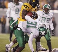 Marshall scored first in the 2009 Friends of Coal Bowl played in Morgantown WV, but was held scoreless thereafter in a 24-7 Mountaineer victory - the ninth in the series without a loss. Here, Noel Devine runs over Omar Brown for a TD.