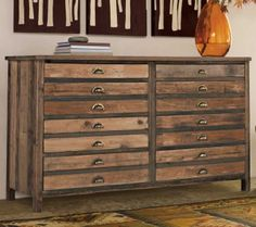 """The patina of our reclaimed elm console embodies timeworn elegance and heritage craftsmanship. Every nick and pockmark adds natural character to the beautiful wood grain. Our clever console conceals eight drawers behind the 14 handles, offering six drawers of double-deep storage and two tray drawers on top. With an admiring nod to the brass-handled file cabinets of old, the console's trim frame updates a proven classic for entryway, dining room or bedroom. 61""""L x 20""""D x 35""""H.   $1275"""