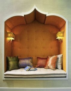 An Indian-inspired book nook, complete with sconces! Lovely!