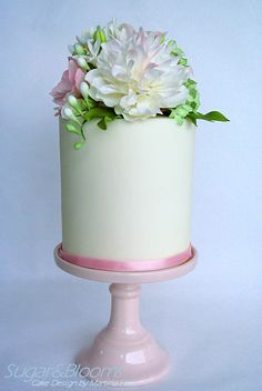 Double barrel cake with sugar flower arrangement in pink, white and green shades.