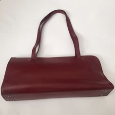 """Furla Handbag Authentic dark red Furla handbag purchased in Venice, Italy. Bag is gently used, leather straps and front and back show signs of kinking due to storage. Backside has a very small blemish. The inside lining has a dark stain all around the top seam and above zipper pocket. I don't know what this. Strap drop is 10.5"""". Price reflects condition. Ships with dustbag. Posh rules, no trade or PP. Offers welcome using offer button. Furla Bags"""
