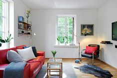 Sleek living room with IKEA small room ideas featuring red couch glass table wall shelves nice planters and sleek black rug