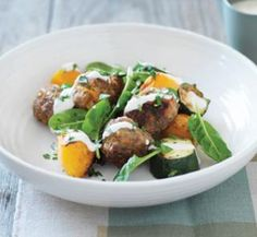 Baked meatballs with yoghurt sauce  750g extra-lean beef mince  1/2 small brown onion, grated  1 small carrot, grated  1/2 cup dried multigrain breadcrumbs  2 tablespoons chopped fresh parsley  1 egg, lightly beaten  2 cups (300g) pumpkin, peeled, cut into 2cm chunks  1 large zucchini, cut into 2cm chunks  olive oil cooking spray  100g baby spinach  Yoghurt sauce  200g tub low-fat natural yoghurt  1 tablespoon tahini (sesame seed paste)