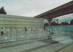Children enjoy running through the water jets on the water plaza