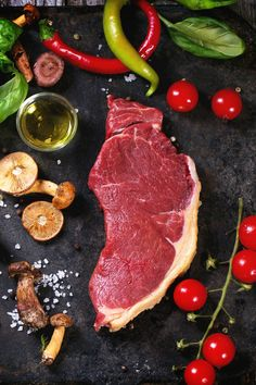Raw steak served with vegetables and forest mushrooms on black metal cutting board over old wooden table.