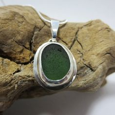 A unique piece of deep forest green sea glass, hand-picked from the coast of Southern California, mounted in a hand crafted .999 fine silver