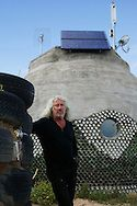 Eco architect MICHAEL REYNOLDS, founder of Earthship Biotecture,  amongst a tire wall foundation and recycled bottle and can building in Taos, New Mexico August 7, 2007...For the past 30 years Reynolds has been designing Earthships-  self-sustained, off-the-grid housing constructed of recycled tires, cans, and bottles.  Reynolds regularly teaches Earthship construction to local builders in countries like Japan, France, Jamaica, and Belize as well as providing disaster relief housing…