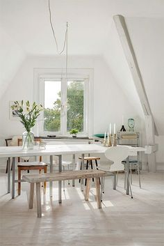 Dining Room decor ideas - modern eclectic Scandinavian style dining room with wood bench, white table and open high ceiling.