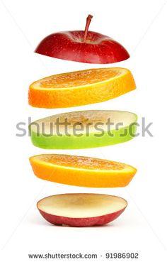 Levitating fresh sliced fruit,  isolated on white - stock photo