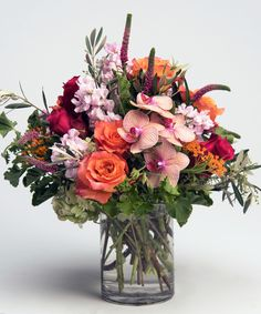 Orange Zest A colorful, gardeny design including roses and orchids is gathered in our signature cylinder vase for this bold burst of Spring.