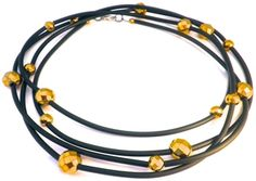 This delicate necklace is made of black rubber cord and gold plated hematite. This piece can be worn in any length.