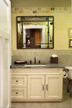 Mudroom bath with onyx tiles and custom decorative painting details and custom steel mirrror
