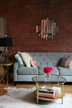 table basse ronde en verre et ferre, mur en briques chaleureux et miroir décoratif