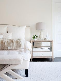 Charming ivory bedroom boasts a mirrored nightstand placed on ebony wood floors against an ivory wall and topped with an ivory double gourd lamp.
