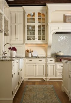 This creamy white country kitchen caught my eye, love the warm wood floors & the herringbone pattern above the range ...
