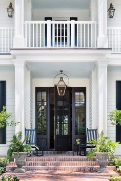 Portico with Rocking Chairs: Black rocking chairs sit on brick pavers on a portico lit by a carriage lantern hung in front of a glass paneled black front door flanked by sidelights. Front Door Entrance, Glass Front Door, Front Entrances, Glass Door, Entry Doors, Entryway, Doorway, Porte Cochere, White Exterior Houses