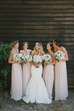 bride and bridesmaids in blush pink full length dresses having a giggle