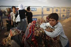 Kurdish Syrian refugees wait with their belongings after crossing the Turkish-Syrian border near the southeastern town of Suruc in Sanliurfa province September 25, 2014.