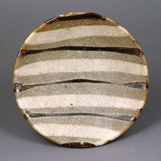 Shoji Hamada  |  Small Dish (ca.1965): Stoneware, cream glaze with grey/brown poured lines across the well (h3.5cm, d18.8cm).